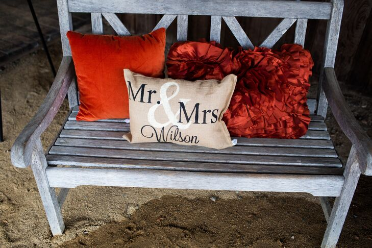 "A wood bench was decorated with red pillows in the back and a burlap pillow in the front that read ""Mr. & Mrs. Wilson."""