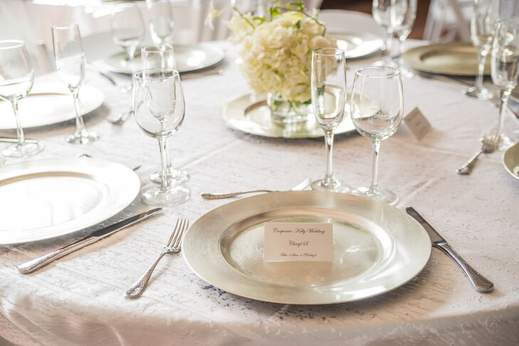 At the reception at Silvan Ridge Winery in Eugene, Oregon, guests found their seats at white-covered dining tables with classic black-and-white escort cards. The stationery perched on top of silver charger plates embodied an elegant look for the classic wedding day.