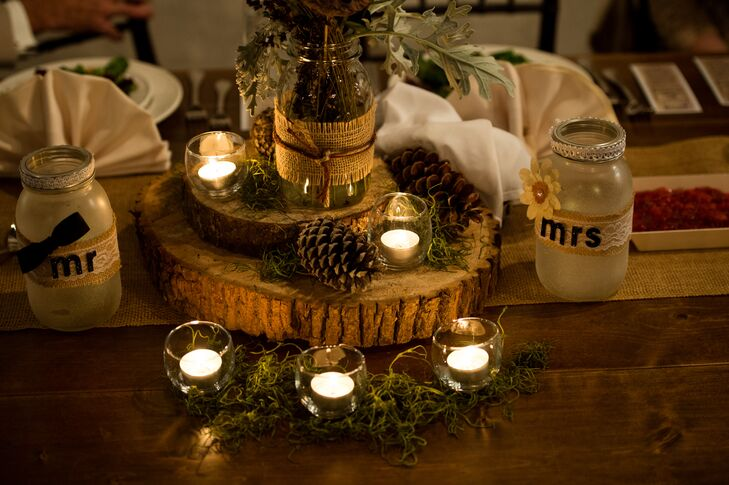 Centerpieces consisted of wood slabs decorated with candles, moss and pine cones. There were also small arrangements of leaves in mason jars. The table runners were made of burlap.