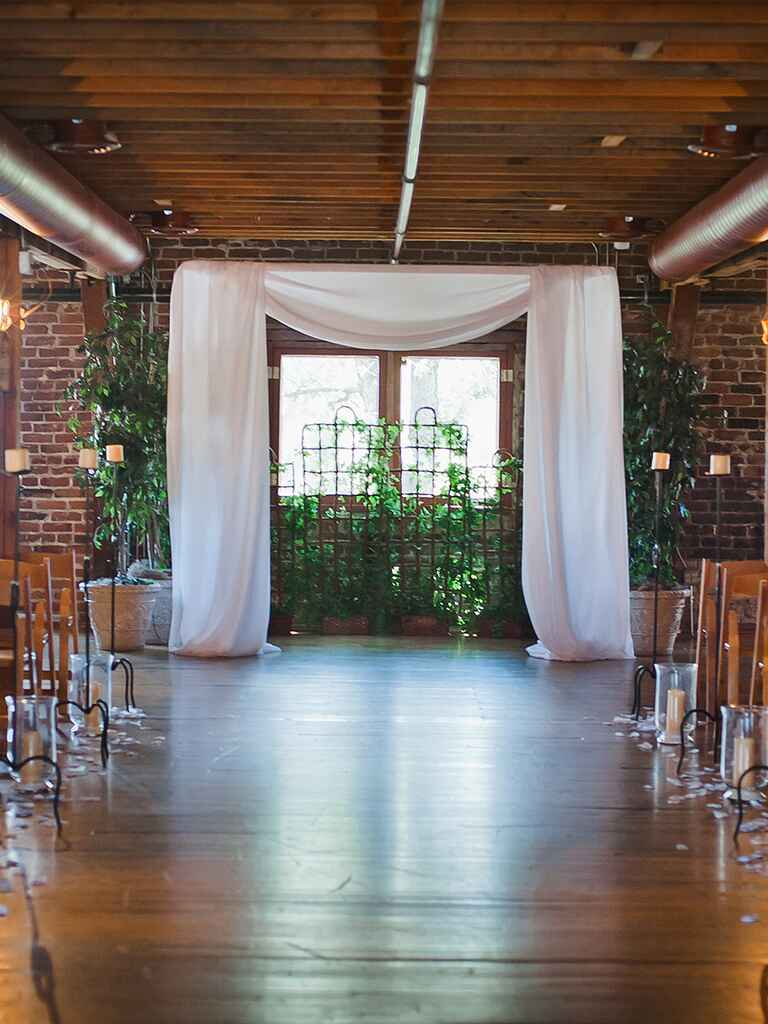 Rustic indoor ceremony with wide, draped white fabric and greenery backdrop