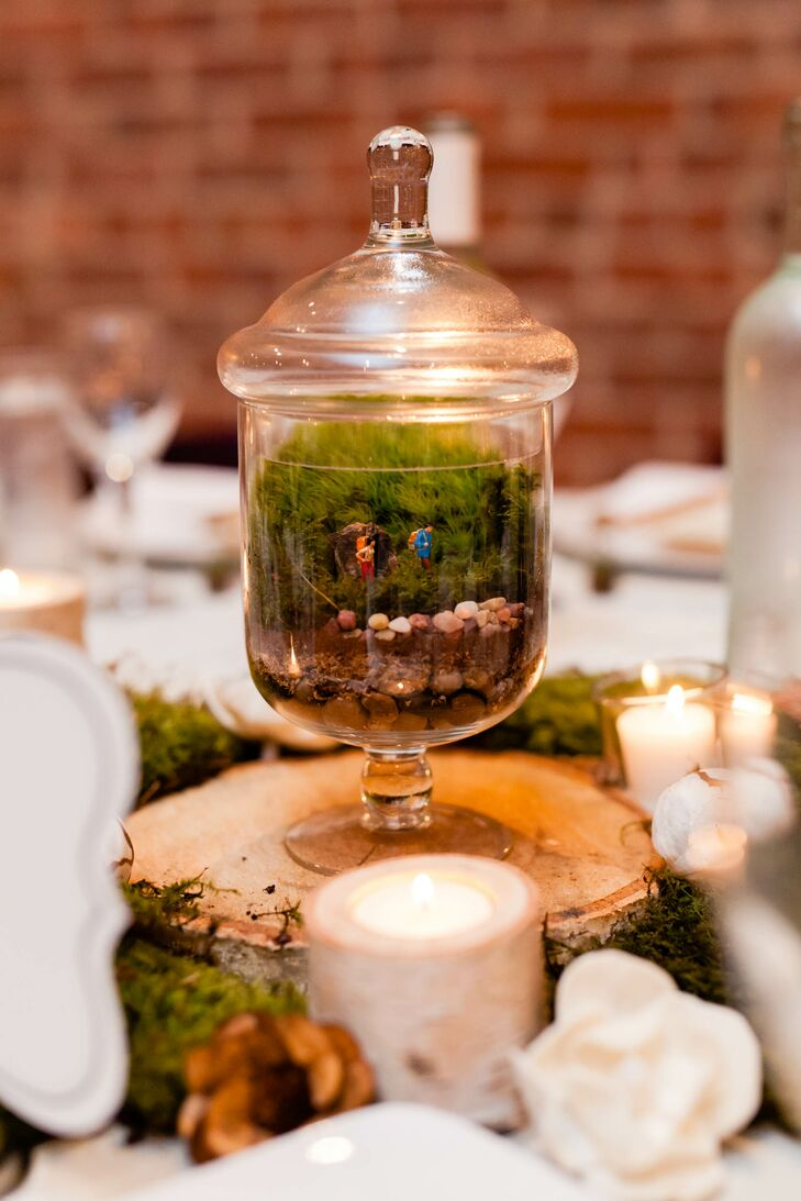 "Instead of decking out their reception tables with arrangements of soft, romantic blooms, Beth and David decided to think a little outside the box when it came to their decor. ""I love moss and terrariums and hate how wedding flowers just get thrown away,"" says Beth, ""so we had terrariums as centerpieces that people could take home afterwards."" The terrariums were made with vintage-inspired apothecary jars, each one unique and displaying a type of outdoor scene. The terrariums were placed on tree slices and surrounded by earthy moss and votive candles in birch holders."
