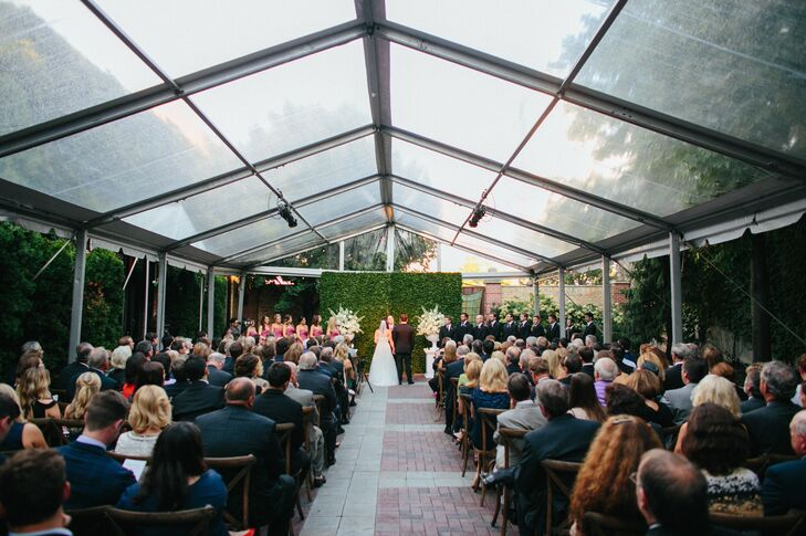 "Liz and Dave wed in an outdoor courtyard at Chicago Illuminating Company against a lush backdrop of green ivy and flanked by two large bouquets. ""I chose the venue because of the courtyard option and loved that it brought an element of the outdoor to our ceremony,"" the bride says. Guests watched on while seated on white, wood grain chairs."