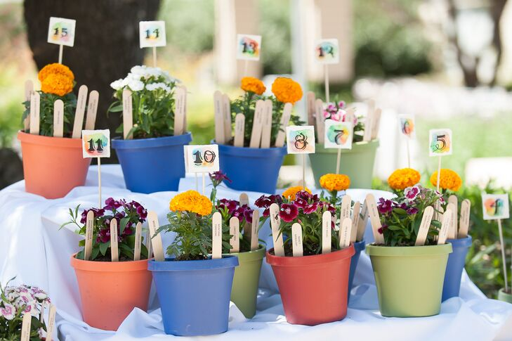 At their garden-party reception, the couple displayed their escort cards on ice-pop sticks inside planters filled with flowers. Christine created the watercolor table numbers herself.