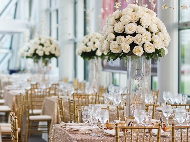 Tall white rose centerpieces at indoor wedding reception venue