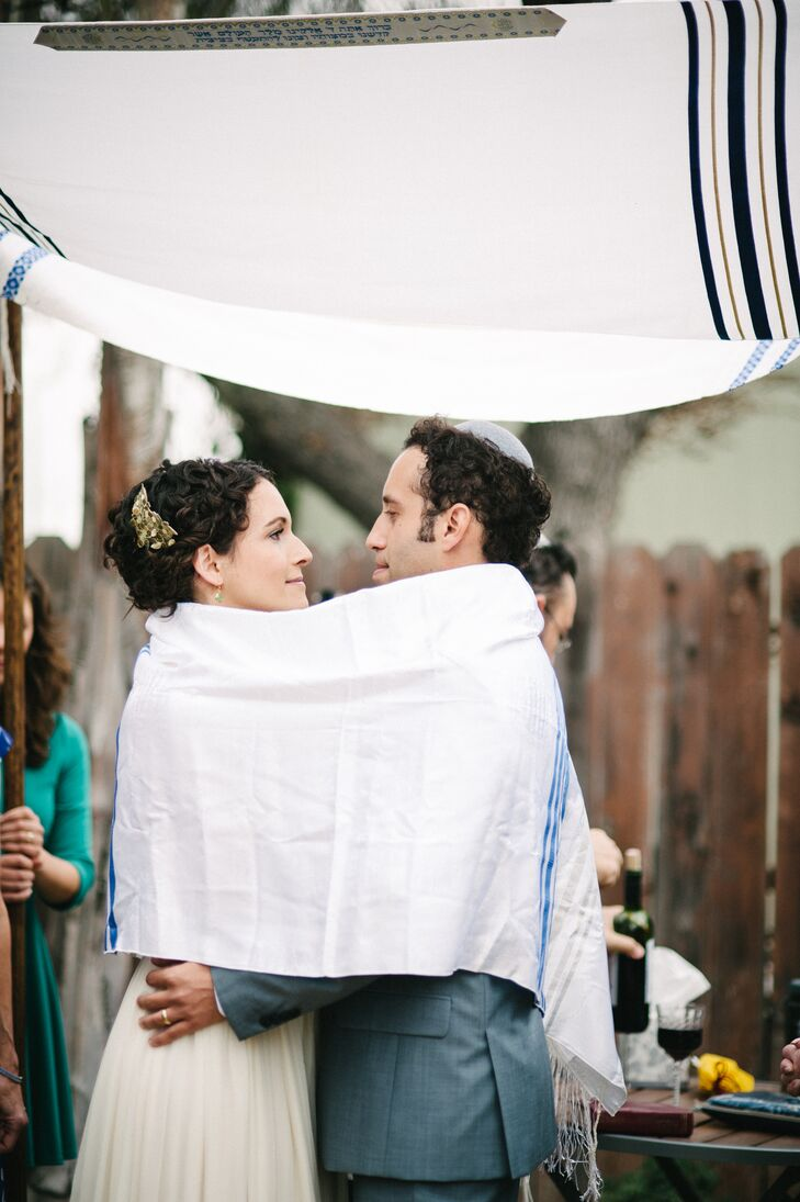 Emily and Chris were wrapped by the tallith during their Jewish ceremony, which took place under their white and blue chuppah. Instead of four poles holding up the Jewish prayer shawl, the couple chose four close family members to hold up the poles, incorporating loved ones into their ceremony.