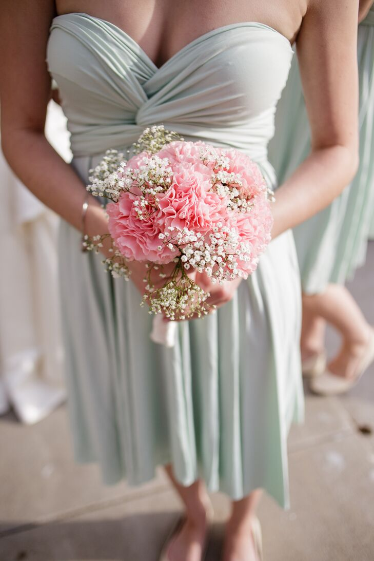 The bridesmaids held bouquets filled with pink carnations and baby's breath, with white cloth wrapped around the stems. They added a pop of soft color to the already soft mint bridesmaid dresses.