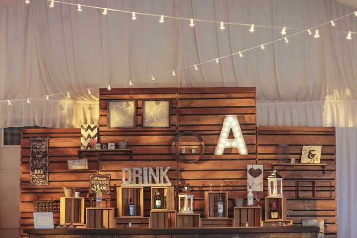 "Inside the reception tent, a wooden bar with lanterns, wooden boxes, a light-up ""A"" and framed images added a rustic vibe."