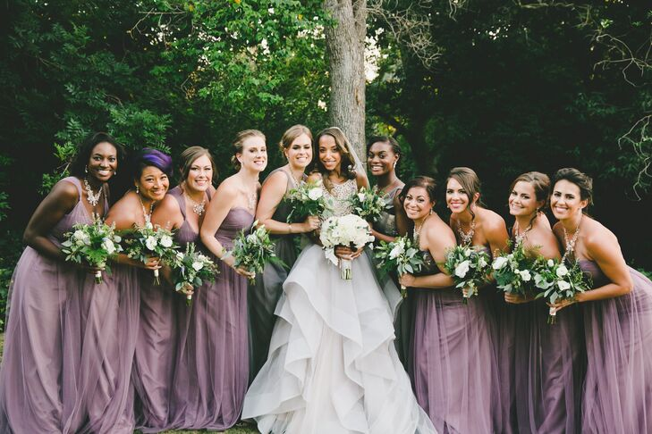 The bridal party's muted lavender and slate dresses alongside the groomsmen's gray tuxedos tied into the event's warm plum and gold palette. Bouquets were a textured mix of champagne and peach roses, sage green succulents, white lisianthus, lavender sprigs and jasmine vines.