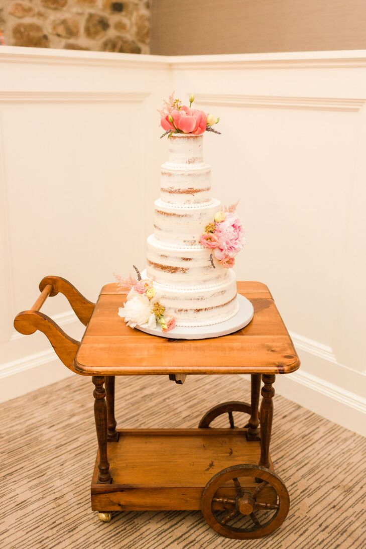 The five-tier cake with white icing and florals was set on a vintage tea cart that Mollie had found on Craigslist.