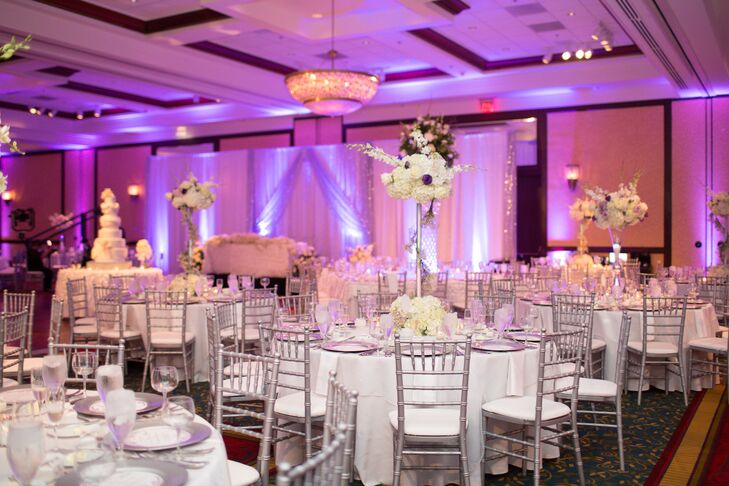 The couple decorated their reception with a variety of white hydrangea and purple roses centerpieces, textured neutral linens atop round tables, silver chiavari chairs and square silver chargers.