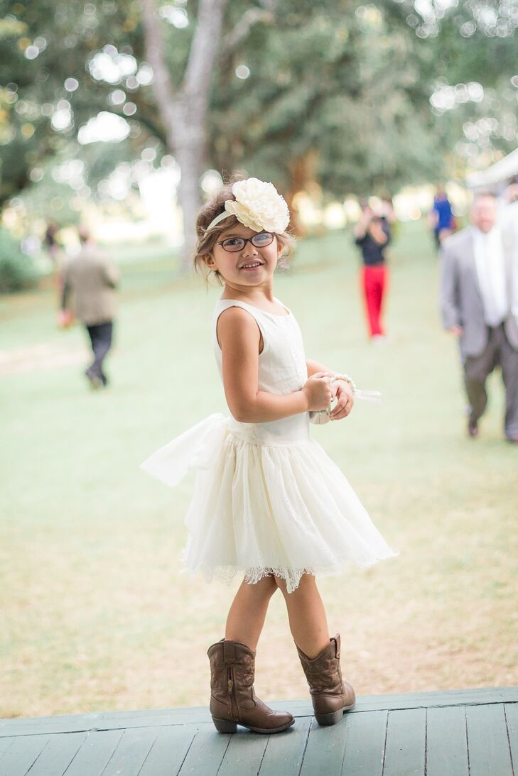The flower girl wore a white A-line skirt and white tank top for the country wedding. Just as Tangie and the bridesmaids did, she completed her look with brown cowboy boots. Wanting to incorporate aspects of Tangie's stunning mermaid-style dress into her look, she donned a gorgeous oversize white peony headband.