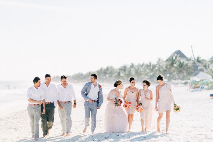 The bridesmaids wore blush and neutral gowns to match the romantic, beachy theme, and the groomsmen dressed in gray pants and white suits with red and pink belts from Beltology. (Since the wedding took place on the sand, everyone went barefoot.)