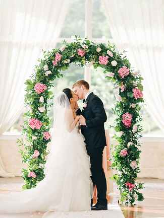 A romantic flower wedding arch wrapped in garlands of greenery and pink hydrangeas