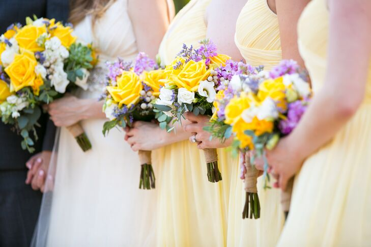 Every bridesmaid paired her soft yellow dress with an extra pop of color. Kansas City Blooms designed their arrangements with yellow roses, white lisianthus, seeded eucalyptus, purple delphiniums, silver brunia and purple statice. Every stem was brought together with a burlap wrap.