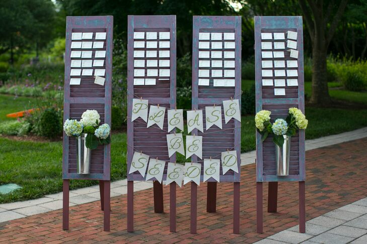 "Escort cards were arranged on vintage shutters with flower arrangements of hydrangeas and a banner that read ""Please Be Seeded,"" a pun on the garden theme."