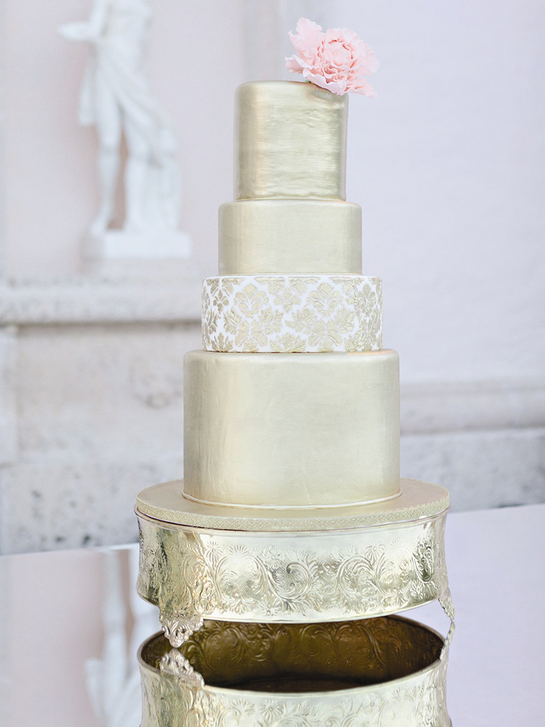 Four tier gold wedding cake topped with a light pink peony