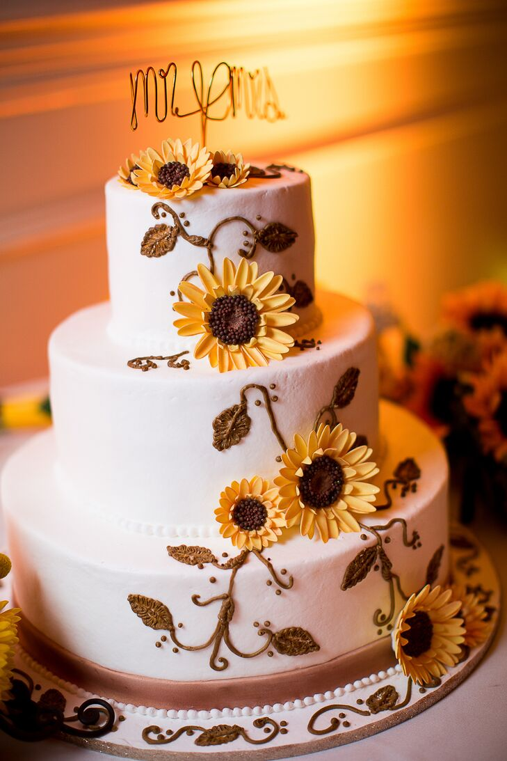 The three tier wedding cake was decorated with sunflower cake flowers.