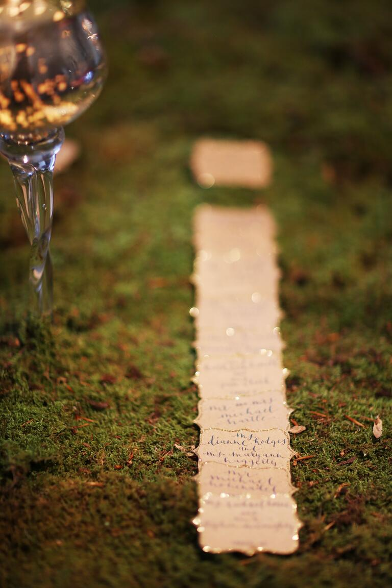Hand Lettered Escort Cards With Glitter Edge on Moss Background