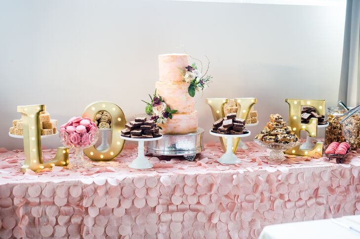 "A beautiful dessert table filled with macarons, Rice Krispies bars, chocolate chip cookies, caramel corn and brownies was decorated in pink and with gold letters spelling ""love."""