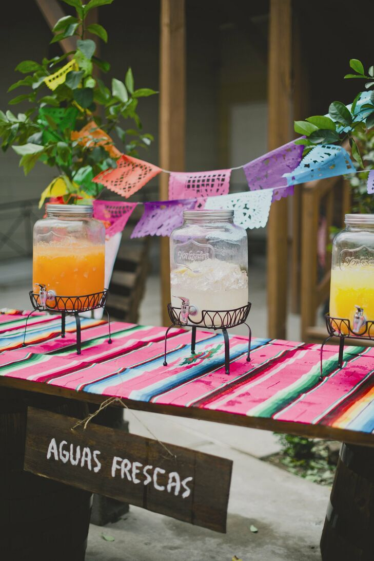 Jars of aguas frescas were displayed on a colorful table runner for the cocktail hour.