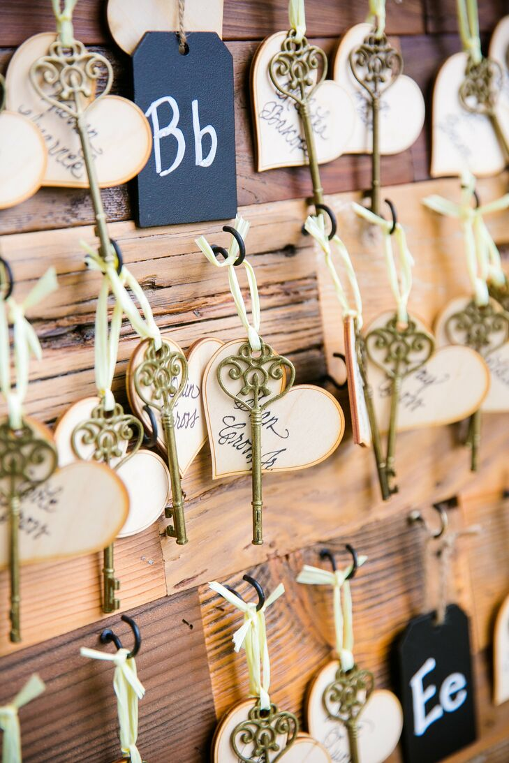 A creative twist on escort cards, Carly and Spencer personalized small wooden hearts with friends' and family members' names and attached them to skeleton keys with pale yellow ribbon.
