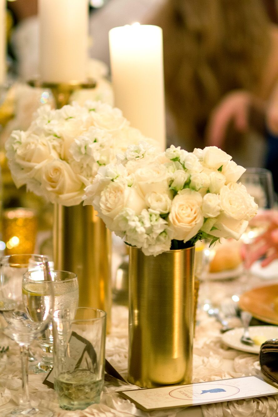 White rose and hydrangea centerpieces in gold vases