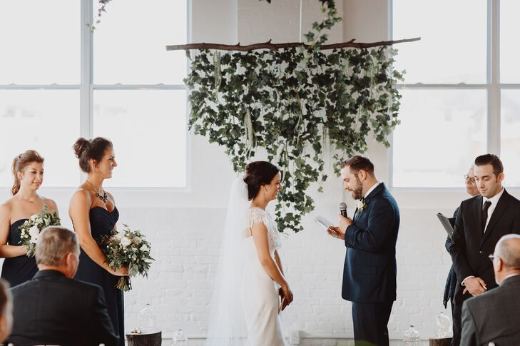 "With its natural wood floors, tall ceilings, whitewashed brick and wall-to-wall windows, Reading Art Works in Reading, Pennsylvania, offered a raw space for Shannon and Jason to make their own. Wanting to highlight the setting rather than detract from it, the couple kept the decor for the ceremony simple, adding only a few wooden logs, fairy lights and a hanging installation with cascading vines and flowers to the space to create a whimsical, rustic backdrop against which to say their ""I dos."""
