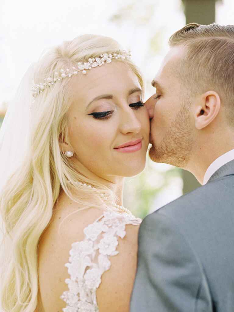 A bride with winged eyeliner getting kissed by her groom