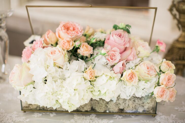 The couple stuck with a neutral palette of white and pale-pink hues for the reception to continue the romantic glam theme. The Lord Thompson Manor in Thompson, Connecticut, used vintage glasses the couple provided to arrange lush bouquets of pale-pink roses, white hydrangeas and anemones at the center of each table.