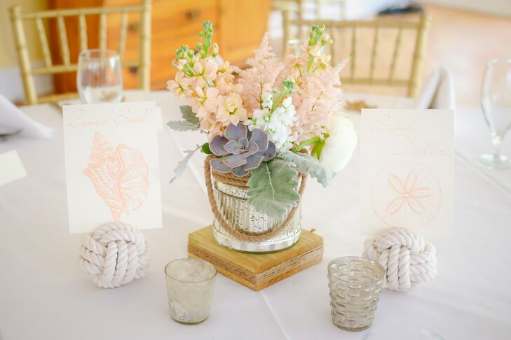 """From the start I had a vision in my head of a whimsical, ethereal and vintage feel mixed with nautical elements,"" says Lindsey. Every table was set  to this notion with a low arrangement of succulents, pink and white delphiniums, dusty miller and pink astilbe inside a silver vase wrapped in rope. Wanting to take the nautical theme a step further, they also had table numbers made of knotted rope and chic seashell-inspired table names."