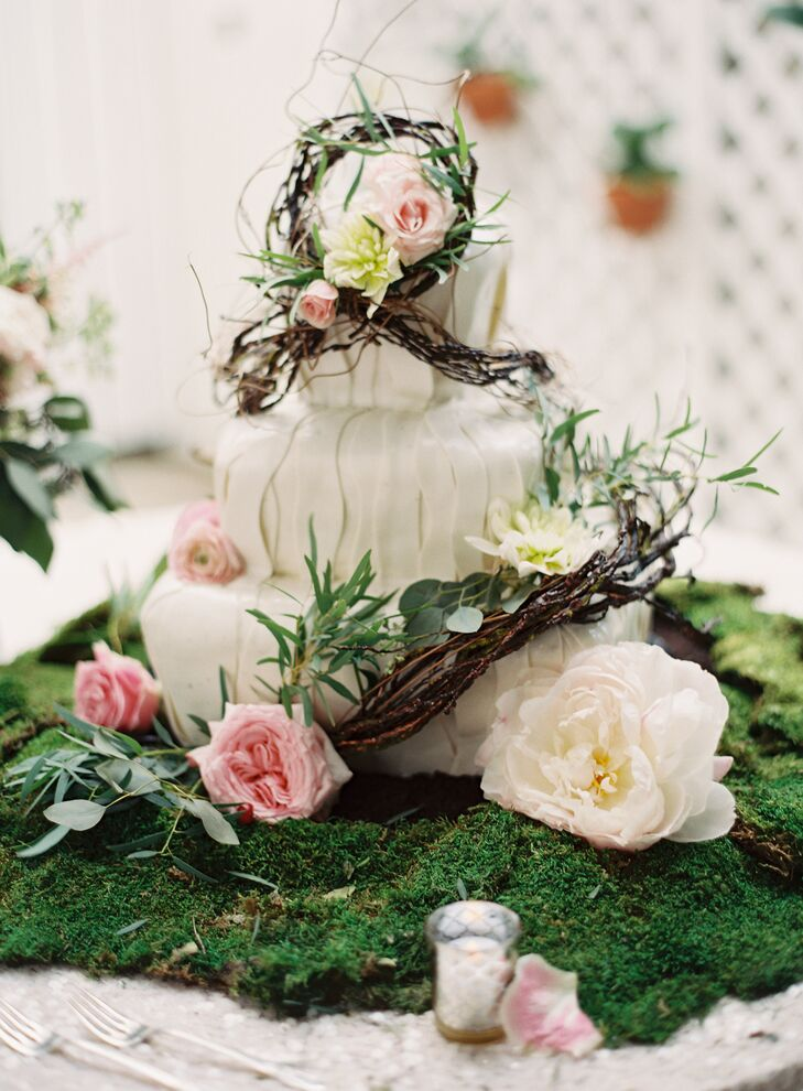 "The couple chose a whimsical garden inspired three-tiered wedding cake baked by Johnson's Custom Cakes & More. It was complemented with cream peonies, pink garden roses and pink ranunculus. ""We wanted the cake to seem as though it were part of the decorated room, and not a foreign piece of focus,"" says Joyce."
