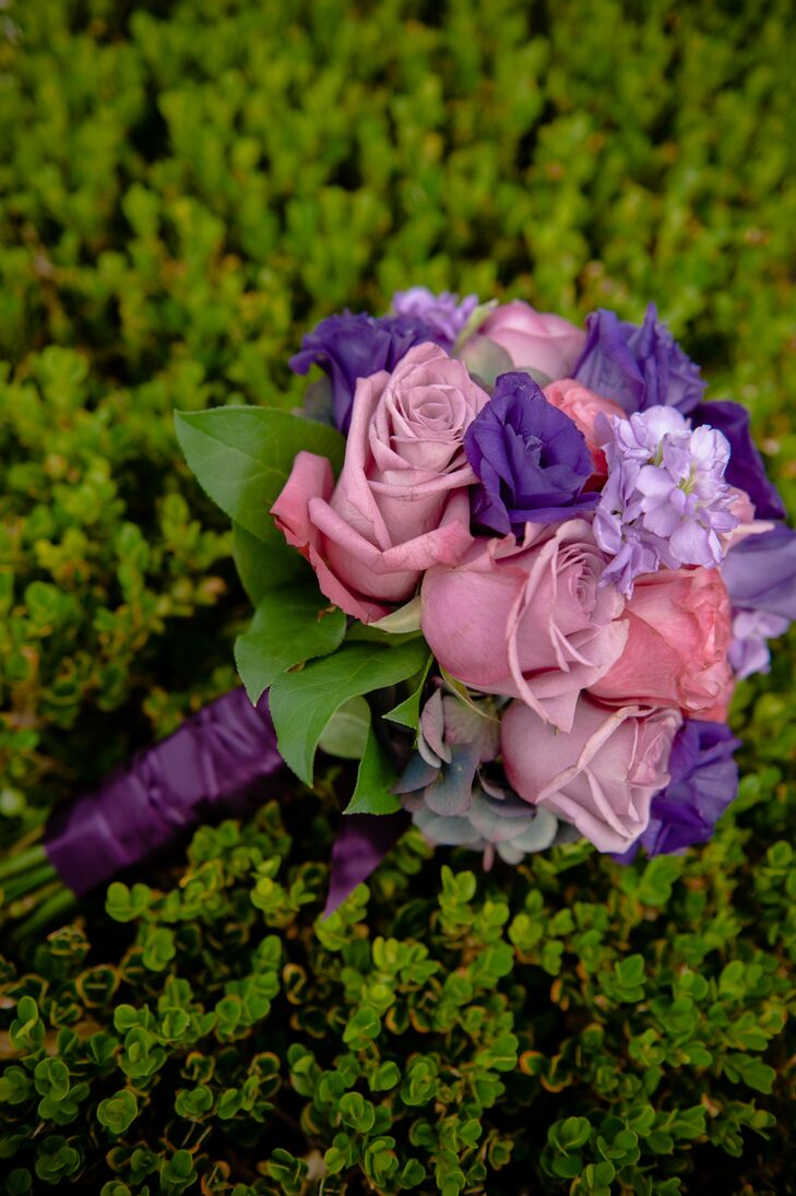 Christine's purple and pink bouquet filled with roses, lisianthus and stock truly embodied the romantic vibe of the wedding day. The flower arrangement had a purple wrap tied around its stems to keep all the flowers together.