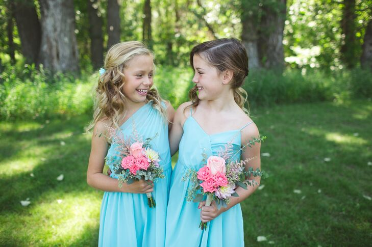 The adorable flower girls wore aqua blue dresses and carried small coral pink bouquets designed by Flower Chix.