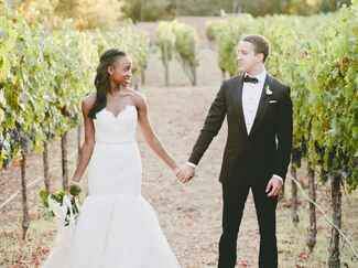 A bride and groom pose in a vineyard