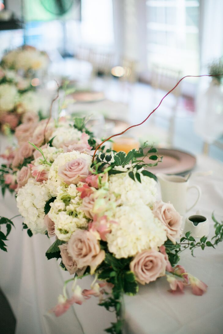 An and Eddie's tented reception garden venue had lush displays of roses, willow tips and other blooms along each table. Their sweetheart tablescape included mauve roses, white hydrangeas, willow tips, greenery and pink lilies of the valley.