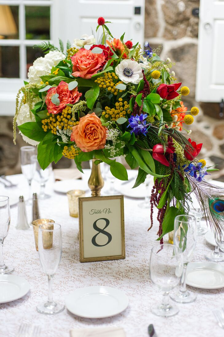 Several guest tables had a gold pedestal arrangement of garden roses, white hydrangeas and anemones, orange dahlias, blue delphiniums, gold coxcomb, red tulips and zinnias accented with amaranths, gomphrenas, yellow craspedias, peacock feathers, sword fern, ruscus and seeded eucalyptus.