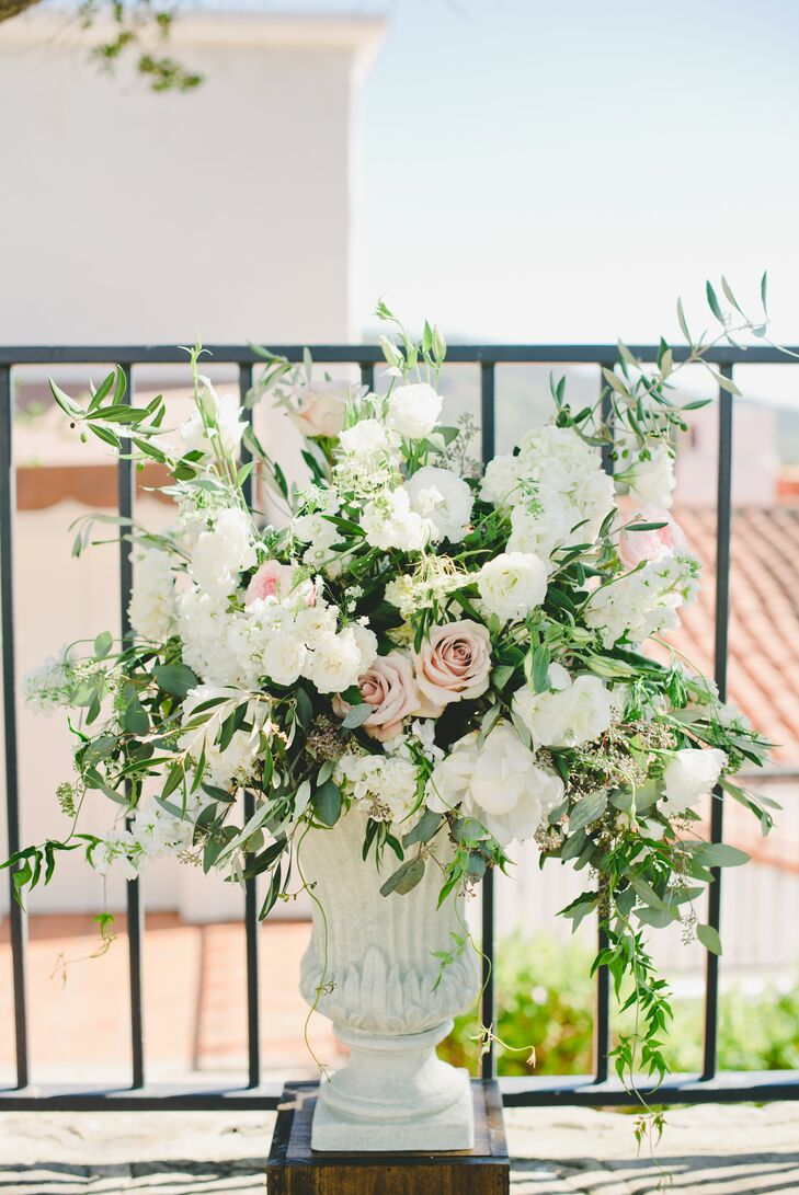 Peony & Plum created the floral arrangements, including this urn filled with white hydrangeas, lisianthus, peach and ivory roses, Queen Anne's lace, eucalyptus, jasmine vines and olive branches.