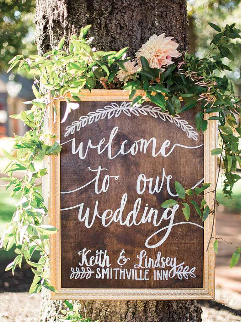 Rustic wooden welcome sign with calligraphy for a wedding