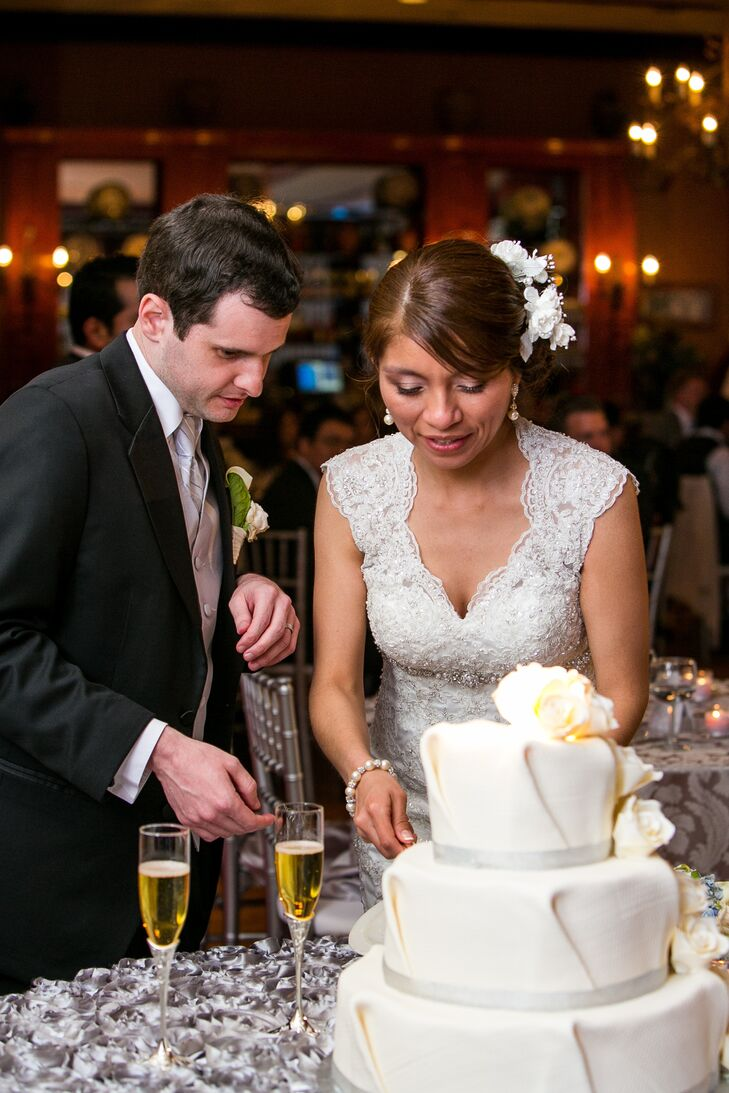 Patricia and Leonard cut the cake at the wedding reception, which was three-tiered ivory wedding cake with silver ribbon wrapped around the bottom of each tier.