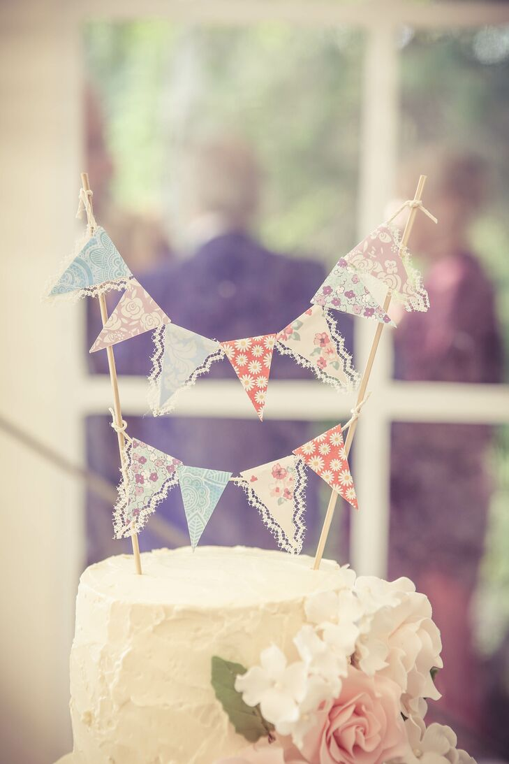 A vintage bunting flag cake topper added a cute touch to the three-tier white buttercream-frosted cake.