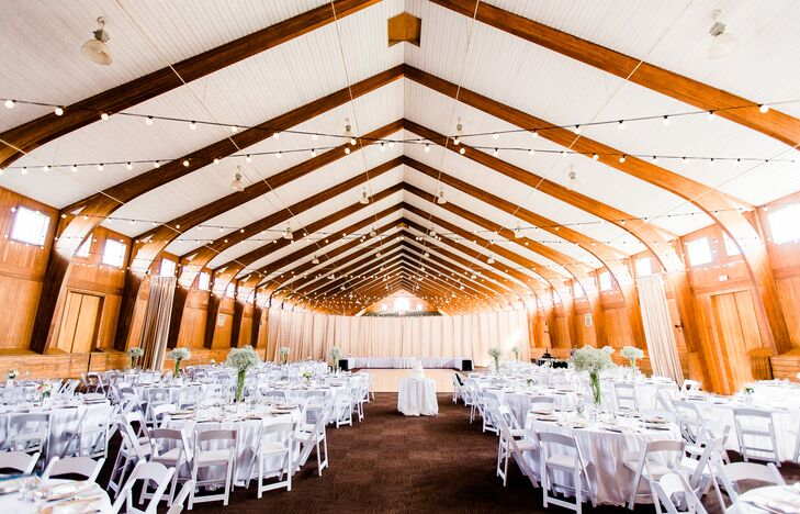 After the beautiful ceremony, the indoor main barn on the property flipped for the reception—thanks to the help of Lauren Ryan Events. Round dining tables filled the space, covered in white linens and decorated with baby's breath centerpieces.