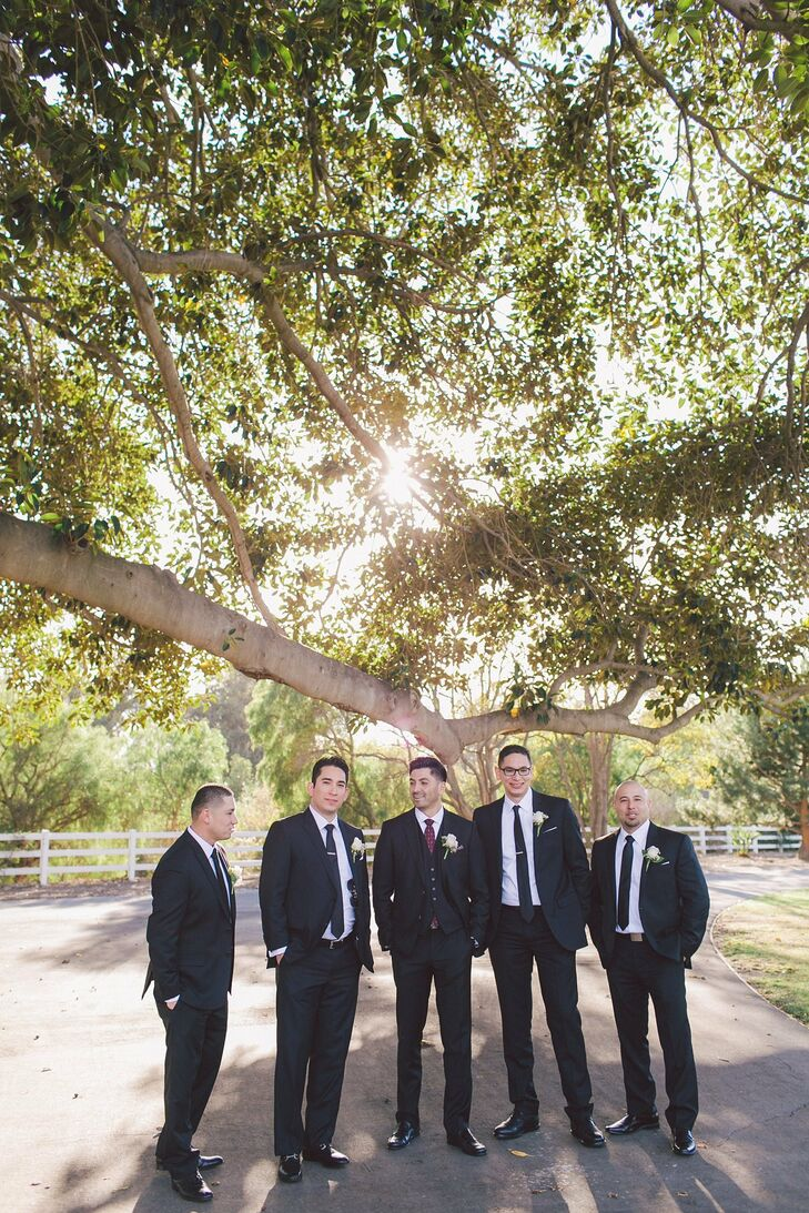 Groomsmen donned traditional black suits with matching ties and boutonnieres, while Emmanuel sported an extra piece in his vest.