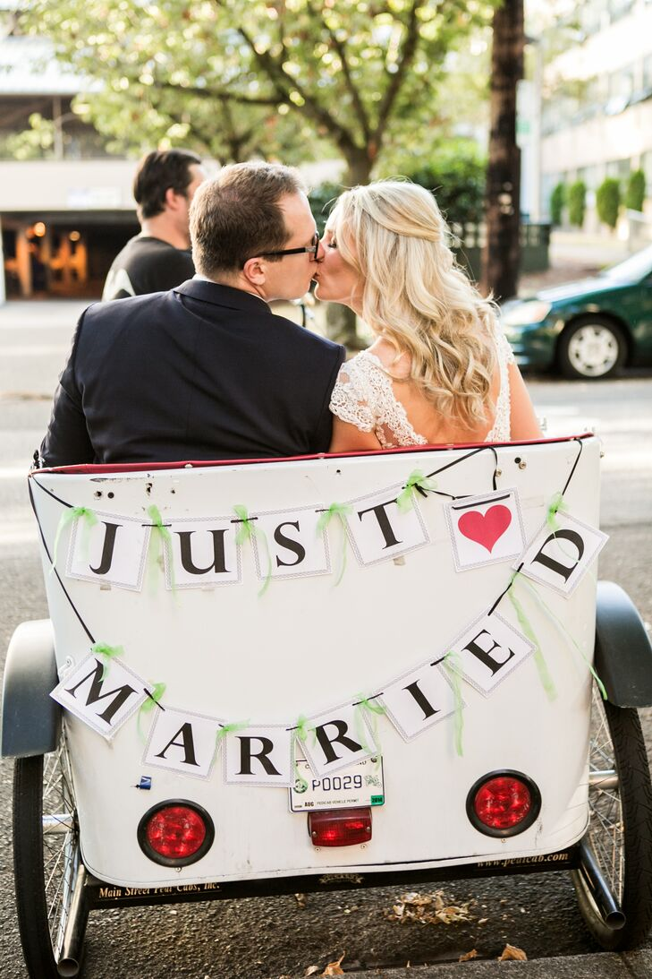"Ashley and Adam made their recessional exit on a white pedicab.  A paper sign was strung on the back of the transportation vehicle, which spelled out ""Just Married,"" accented with a pink heart. Ashley had her hair in a half-up style, which draped down her back."