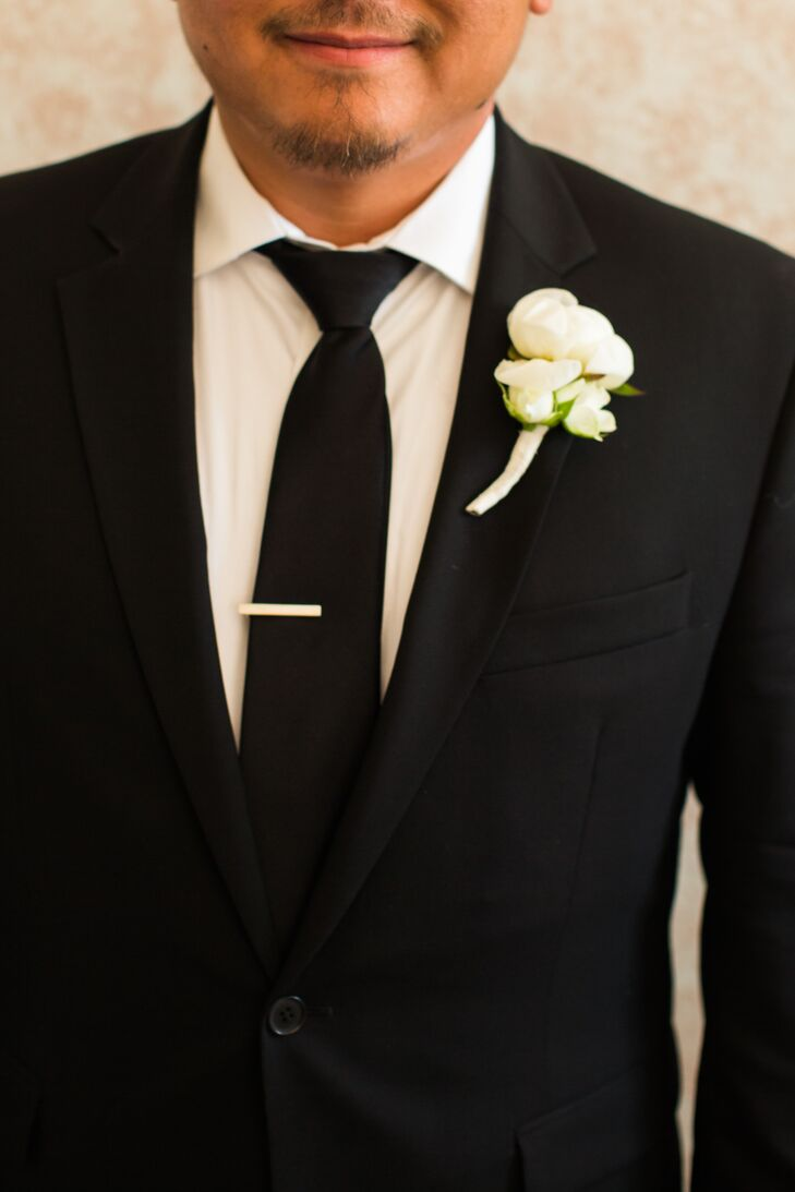 Lan wore a classic black suit with a matching black tie over a white collared dress shirt. He had an ivory rose boutonniere pinned to the lapel of his jacket.