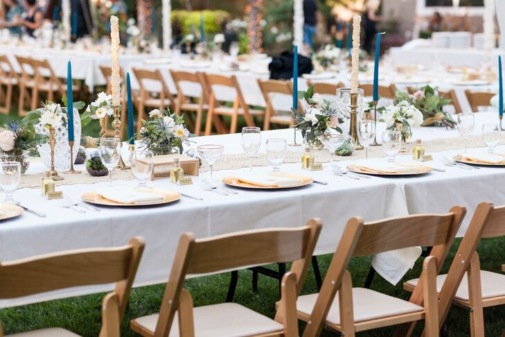 The reception took place in the backyard on Annie's family's property, where long dining tables covered in white tablecloths were set up for guests to be seated at. Each place setting had a gold plate with a white napkin, and the tables were decorated with a variety of wildflowers and candles.