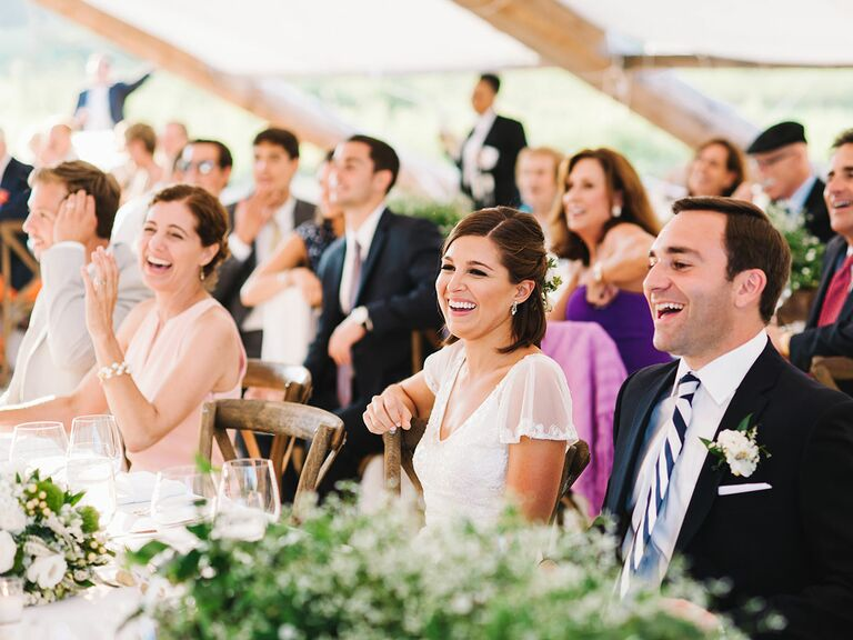 Bride and groom laughing during a toast