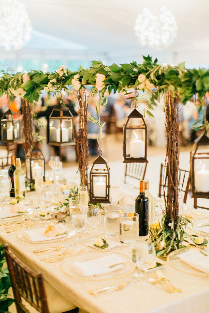 A simple salal and olive branch garland was suspended on the back of Lauren and Kent's chairs. A garland of seeded eucalyptus, mock orange, wisteria, camellia leaf, magnolia, an olive branch with a combination of artichokes, peach and soft pink garden and spray roses and collections of votive, taper and pillar candles decorated the head table.
