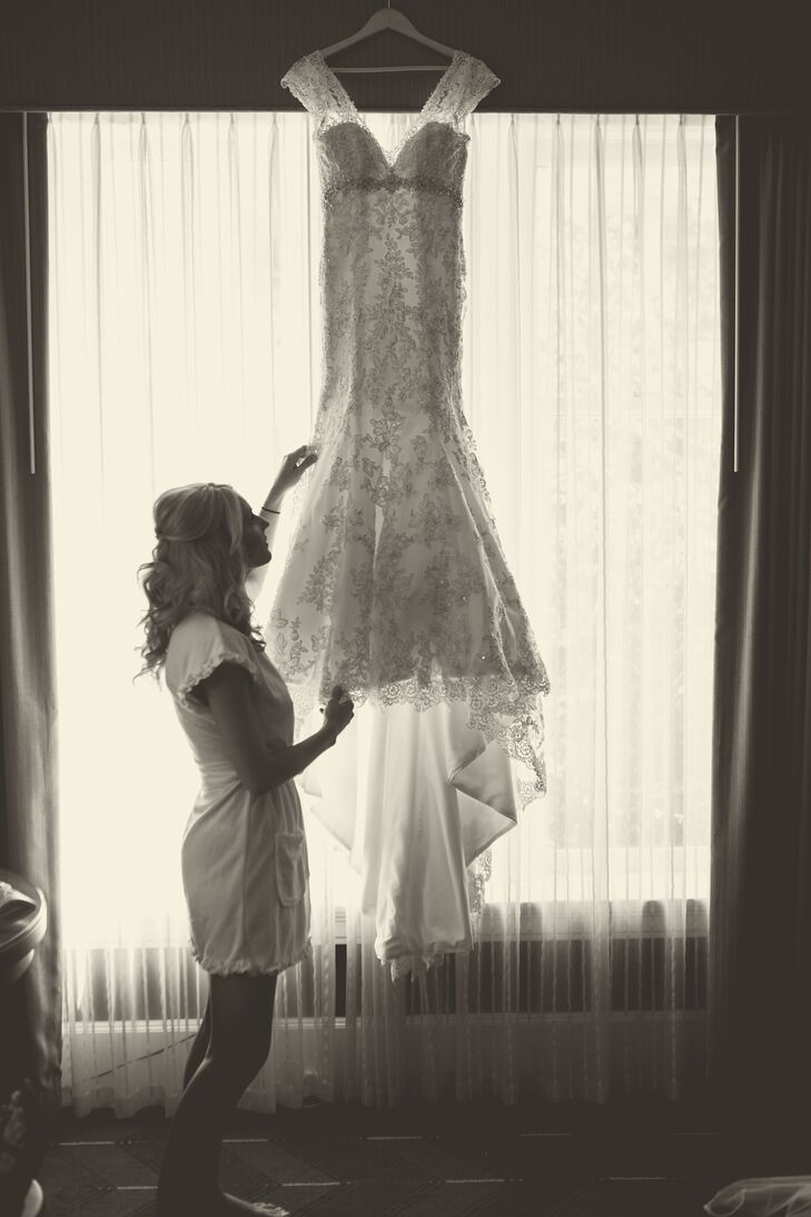 As Ashley was getting ready, she stood next to her ivory wedding dress that was hanging in front of a window. The dress was entirely covered with a lace overlay that draped down to the long train, and had capped sleeves that were accented in lace as well. An elegant crystal belt wrapped around the waist of the dress, adding an extra sparkle to the classic look.
