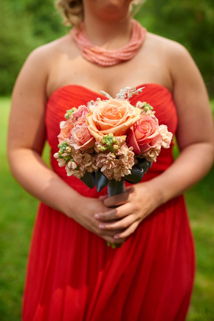 The bridesmaids carried beautiful bouquets filled with coral roses, arranged by Sweet Peas Floral.