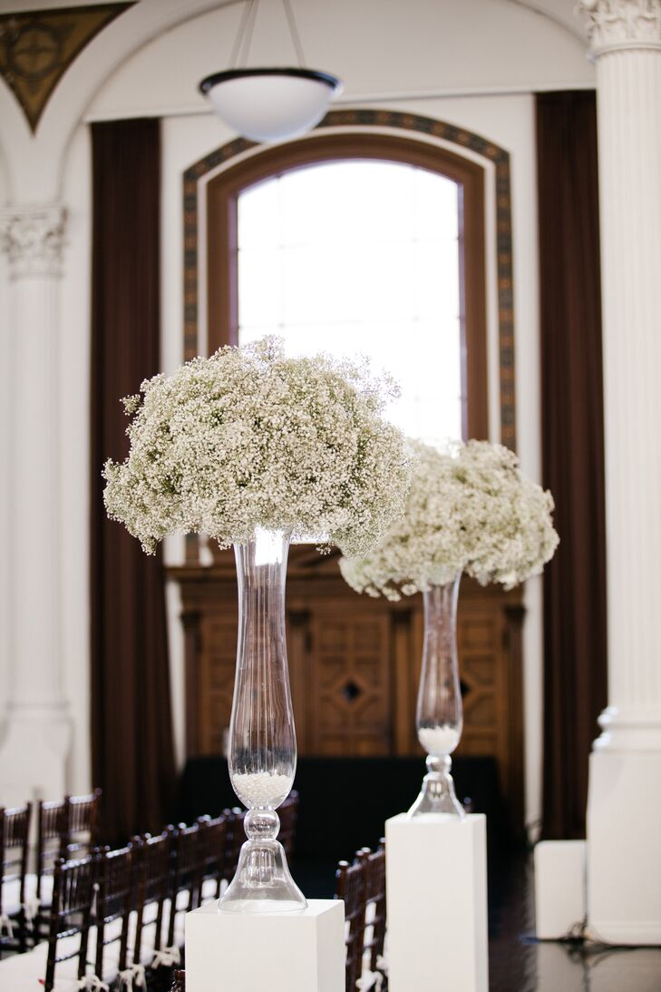 "The ceremony took place inside the Great Hall at Vibiana in downtown Los Angeles, California. The aisle was lined with white pillars, which held up tall glass vases filled with round arrangements of baby's breath. ""Large bouquets of baby's breath in tall acrylic vases lined the aisle, which then doubled as our head-table centerpieces during the reception,"" Stephanie says."